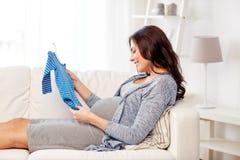 在家拿着男婴紧身衣裤的愉快的妇女 免版税库存图片