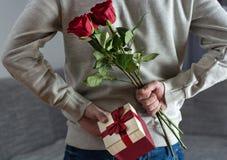 在家拿着红色玫瑰色花和礼物盒在他的后面后的人 免版税库存图片