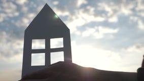 在家拿着纸模型在领域的手特写镜头在日落 纸房子的剪影光芒的  股票录像