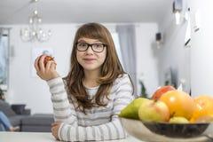 在家拿着苹果的十几岁的女孩画象 免版税库存照片