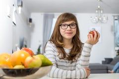 在家拿着苹果的十几岁的女孩画象 库存图片