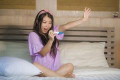 在家拿着预报因子和检查在妊娠试验的年轻愉快的激动的怀孕的亚裔韩国女人正面结果感觉b 免版税库存图片