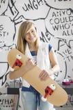 在家拿着滑板的愉快的十几岁的女孩画象  免版税库存图片