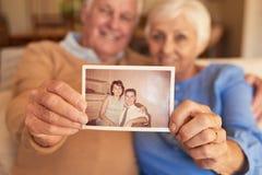 在家拿着他们年轻的照片的资深夫妇的手 免版税库存照片