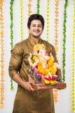 在家拿着Ganesh神象, Ganesh的Chaturthi/节日欢迎上帝的种族穿戴的印地安英俊的人与愉快的expressi 免版税库存图片