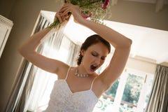 在家掀动恼怒的新娘投掷的花束的图象 图库摄影