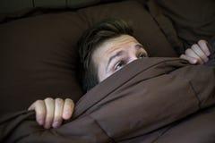 在家掩藏在床的白种人年轻人在毯子下 库存图片