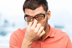 在家摩擦眼睛的镜片的疲乏的人 免版税库存图片