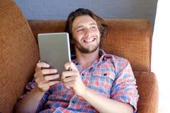 在家放松与一种数字式片剂的微笑的年轻人 免版税图库摄影