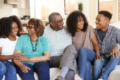 在家放松与他们青少年和年轻成人孙的祖父母 免版税库存照片