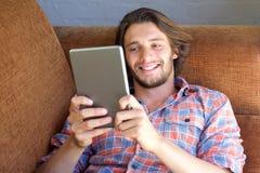 在家放松与数字式片剂的愉快的年轻人 库存照片