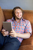 在家放松与数字式片剂的英俊的年轻人 库存图片