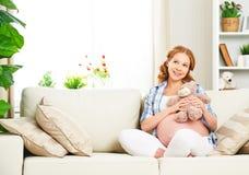 在家放松与玩具玩具熊的愉快的孕妇 免版税库存照片