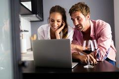 在家放松与膝上型计算机的年轻夫妇 爱、幸福、人们和乐趣概念 图库摄影