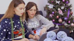 在家放松两个的女朋友和在互联网做圣诞节购买 股票视频