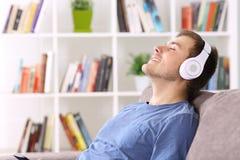 在家放松听到音乐的人 免版税库存图片