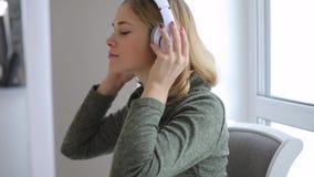 在家放松听的好音乐的妇女,给耳机穿衣 股票视频
