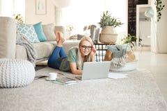 在家放松和使用膝上型计算机的愉快的年轻女人 免版税库存照片