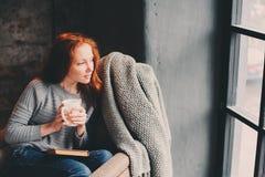 在家放松在与书和杯子的舒适冬天或秋天周末的愉快的红头发人妇女热的茶,坐在软的椅子 免版税库存图片