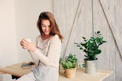 在家放松在与咖啡的懒惰周末早晨的美丽的年轻女性妇女 免版税库存图片