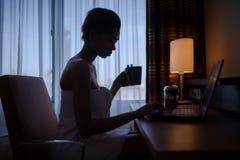 在家放松在与膝上型计算机的浴以后的妇女 图库摄影