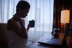 在家放松在与膝上型计算机的浴以后的妇女 库存图片