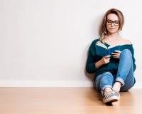 在家放松在地板上的年轻白肤金发的妇女 库存图片