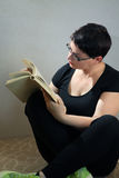 在家放松在地板阅读书的妇女 免版税图库摄影