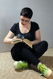 在家放松在地板阅读书的妇女 图库摄影