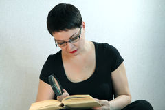在家放松在地板阅读书的妇女 免版税库存图片