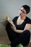 在家放松在地板阅读书的妇女 库存照片