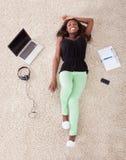 在家放松在地毯的妇女 免版税库存图片