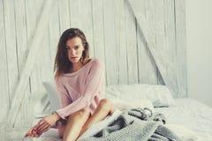 在家放松在床上的桃红色女用贴身内衣裤的年轻性感的妇女 库存图片