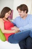 在家放松在有怀孕的妻子的沙发的人 库存照片