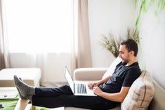 在家放松在有膝上型计算机的沙发的年轻人 库存图片