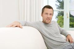 在家放松在沙发的人。 免版税库存照片