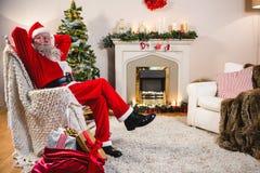 在家放松在沙发的圣诞老人在客厅 免版税库存照片
