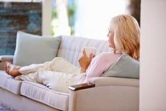 在家放松在沙发的成熟妇女看电视 图库摄影