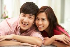 在家放松在沙发的新中国夫妇 免版税库存照片