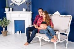 在家放松在沙发的美好的怀孕的夫妇一起 愉快的家庭、期待孩子的男人和妇女 免版税库存照片