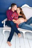 在家放松在沙发的美好的怀孕的夫妇一起 愉快的家庭、期待孩子的男人和妇女 图库摄影