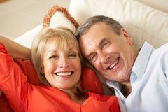 在家放松在沙发的高级夫妇 免版税库存照片