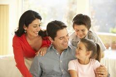 在家放松在沙发的年轻西班牙家庭 免版税库存图片