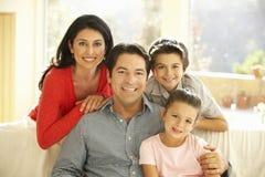 在家放松在沙发的年轻西班牙家庭 免版税库存照片