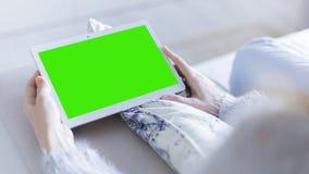 在家放松在片剂计算机上的妇女读书 库存图片