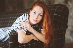 在家放松在秋天的年轻美丽的红头发人妇女画象  库存照片