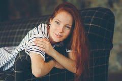 在家放松在秋天ot冬天舒适晚上的年轻美丽的红头发人妇女画象  库存图片