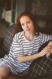 在家放松在秋天ot冬天舒适晚上的年轻美丽的红头发人妇女画象  免版税库存照片