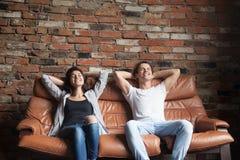在家放松在舒适的皮革长沙发的年轻愉快的夫妇 免版税库存图片