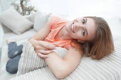 在家放松在长沙发的年轻女学生 库存图片
